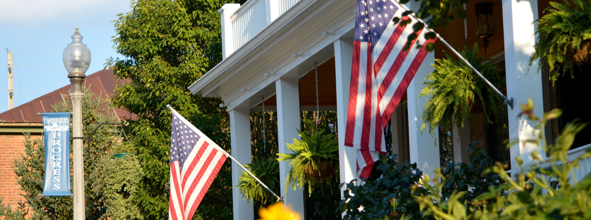 American flags in front of porch pillars